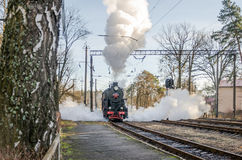 Old iron black retro vintage Soviet steam locomotive with red star arrives at the railway station to board passengers in the clou Royalty Free Stock Image