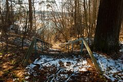 Old Iron Blue Staircase, Descending To River. Old Iron Blue Staircase With Dry Leaves, Tree Branches And Snow Melts, Descending To River In Forest At Spring Top Royalty Free Stock Photo