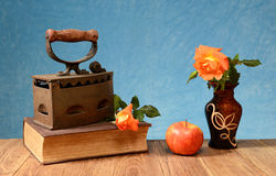 Old iron, books, apples and flowers Royalty Free Stock Images