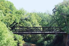 Old Iron Bridge Across River. Old abandoned iron bridge in Oklahoma, crossing over river, surrounded by green trees stock photos