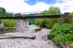 Old iron bridge over the river on a background of forested hills stock photo