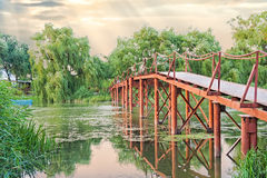 Old iron bridge on the river at sunset Stock Photos