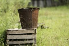 An old iron bucket at wooden pallet Royalty Free Stock Photography
