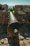Old iron cannon aiming through crenel in wall at the Marvao Castle. Close-up of old iron cannon aiming through crenel in the stone outer wall, on sunny day at royalty free stock image