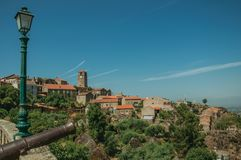 Old iron cannon in front of the Monsanto village on top of hill. With stone steeple and houses. This township is considered one of the cutest and most peculiar stock image