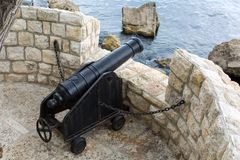 Old iron cannon pointing out to sea defending a castle Royalty Free Stock Photo