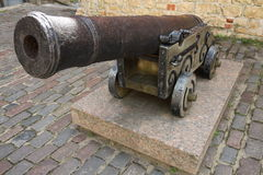 Old iron cannon in Riga. Staying before wall Royalty Free Stock Photos