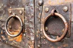 Old iron-clad doors with rusty metal ring handles.  stock photos