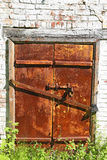 Old iron closed door  on  brick wall. Royalty Free Stock Image