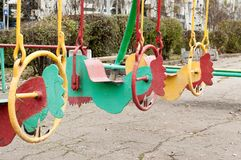 Old, iron multicolored swings for children Stock Image