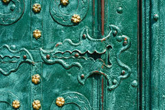 Old iron door, forged and painted in green color with golden flowers for background, vintage style, retro elements Royalty Free Stock Photo
