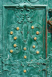 Old iron door, forged and painted in green color with golden flowers for background, vintage style, retro elements royalty free stock images