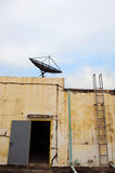 Old iron door and satellite dish. Old iron door and old office wall will see satellite dish on top Royalty Free Stock Image