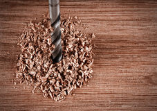 Old iron drill bit makes a hole in wood. Old iron drill bit makes hole in a wood Stock Images