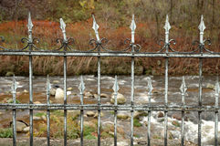 Old iron fence. Old devastated iron fence on river bank royalty free stock photos