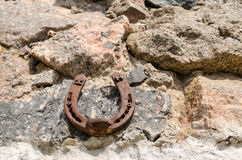 Old iron fortune symbol horseshoe on stone wall Stock Photo