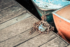 Old iron frayed and shabby boat noses tied to wooden dock Stock Photo