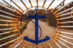An old iron gate decorated with an emblem of an anchor. Concept: security and protection royalty free stock photos