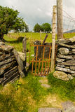 Old iron gate stile in dry stone wall Royalty Free Stock Photos
