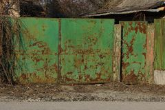 Old iron green gates in rust and dry vegetation outside. One old iron green gate in rust and dry vegetation outside stock photography