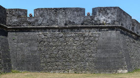 Old iron guns positioned on the huge wall of Forte de Santa Catarina do Cabedelo in Joao Pessoa city. Historic place and objects o Stock Images