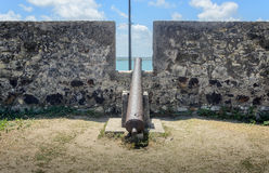Old iron guns positioned on the huge wall of Forte de Santa Catarina do Cabedelo in Joao Pessoa city. Historic place and objects o Royalty Free Stock Photography