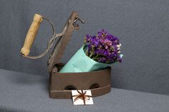 Old iron, heated by hot coals. A bouquet of dried flowers is embedded in the slightly open iron. Nearby is a greeting card.  stock image