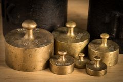 Old iron 1kg weight and smaller brass weights for a kitchen scale. Standing on a table royalty free stock photo