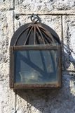 Old iron lantern with a candle in the wall Stock Photography