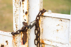 Old iron lock hangs on a rusty gate closed Royalty Free Stock Photos