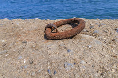 Old iron mooring cleat on a concrete pier Royalty Free Stock Photos