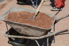 Old iron mortar cart full of sand. Shovel is stabbed into the sand. Photo was taken on a nice sunny day. Time: about noon. Photo was taken on a construction site stock image
