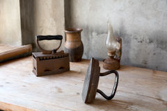 The old iron, oil lamp and jug on a  table. The old iron, oil lamp and jug on a wooden table Royalty Free Stock Photo