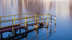 Old iron pier on the frozen pond Royalty Free Stock Photo