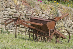 Old iron plow. Disused iron plow is rusting in a meadow Royalty Free Stock Photos