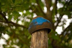 Old iron pot hanging to dry on a wooden column Stock Images