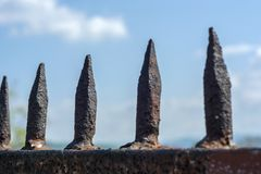 Old iron prison spikes and blue sky Royalty Free Stock Image