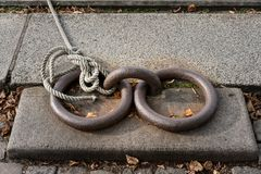 Old iron rings with rope and knot mooring a boat Stock Image