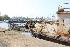 Old Iron Rusted boats in dry dock for repairs. Iron steel boat on shore shallow water in Mumbai dockyard, Maharashtra, India Stock Photos