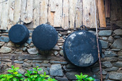 Old iron skillets and antique pans hang on a wall Stock Photo