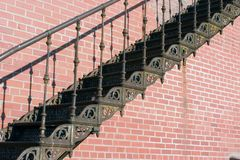 Old iron stairs. A section of some old rusty stairs on a red brick building stock photo