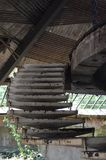 Old iron stairs in an abandoned building. Old concrete stairs on hangers inside the crumbling building of the former dining room ,with exposed wooden rafters and stock photography