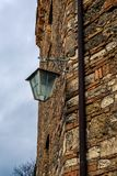 Old iron street lamp hanging ion the side of a wall - 1 Stock Image