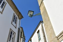 Old iron street light. White stone walls with wood windows. Santiago de Compostela, Spain. Sunny day, blue sky. royalty free stock photography