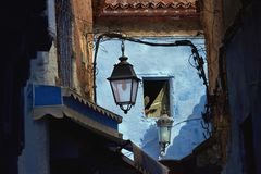 Old iron street lights against blue walls of the medina Chefchaouen, Morocco. Old iron street lights against the blue walls of the medina Chefchaouen, Morocco Royalty Free Stock Photo