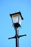 Old iron streetlight against a blue sky. Stock Photo