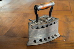 Old iron with wood handle on wood table Royalty Free Stock Photos