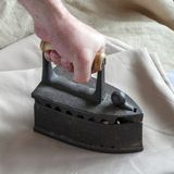 Old ironing iron of the past centuries in a man`s hand. stock images