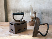 Old irons and oil lamp on  table Royalty Free Stock Images