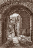 Old Italian alley. Picturesque old narrow alley with archway and drinking fountain in the ancient town Gualdo Cattaneo, Umbria, Italy - black and white image in Royalty Free Stock Photos